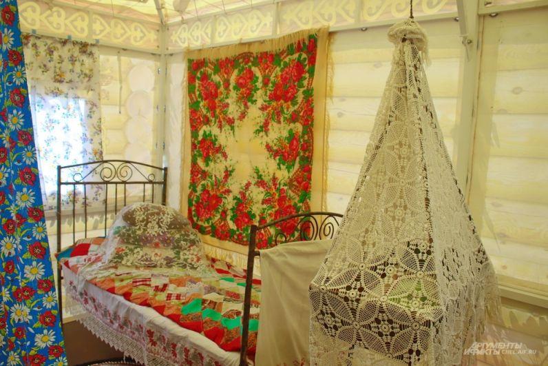 Другой уголок избы: хозяйская кровать, а рядом - подвесная люлька.
