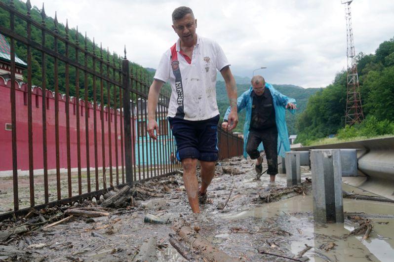 Люди идут по затопленной улице после схода селевых потоков около этнографического комплекса «Моя Россия» в Сочи.