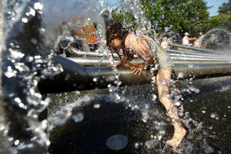 Девочка играет в фонтане в Кельне.