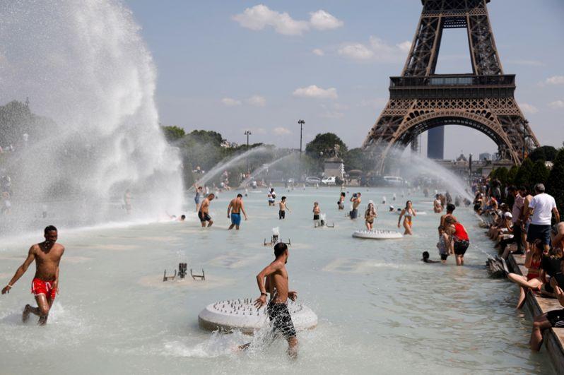 Люди освежаются в фонтанах Трокадеро напротив Эйфелевой башни в Париже.