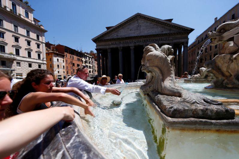 Люди освежаются у фонтана в центре Рима.