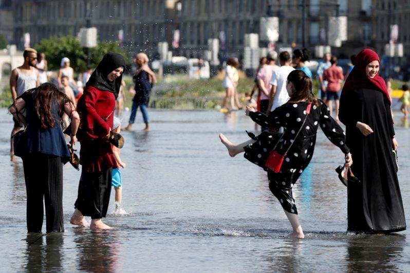 Люди в фонтане «Зеркало воды» в Бордо.