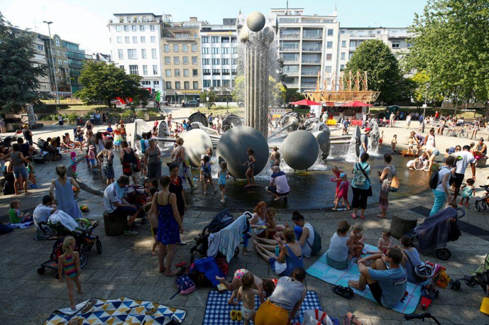 Люди отдыхают рядом с фонтаном на площади в Кельне.