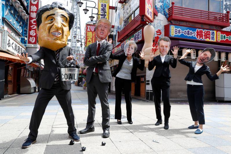 Протестующие в масках участников G20 во время акции протеста.