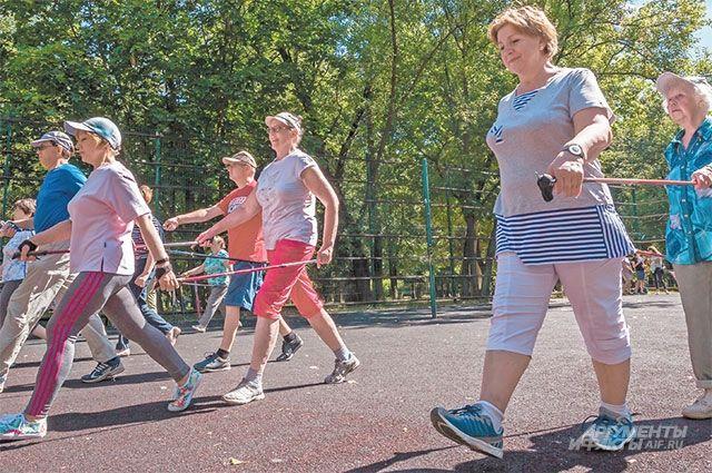 Пенсионеры Академического выполняют разминку перед уроком скандинавской ходьбы.