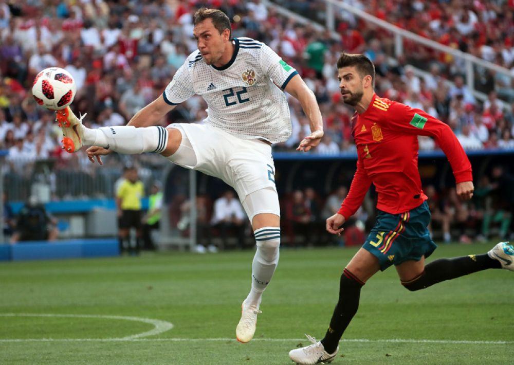 Артем Дзюба (Россия) и Жерар Пике (Испания) в матче 1/8 финала чемпионата мира по футболу между сборными Испании и России.