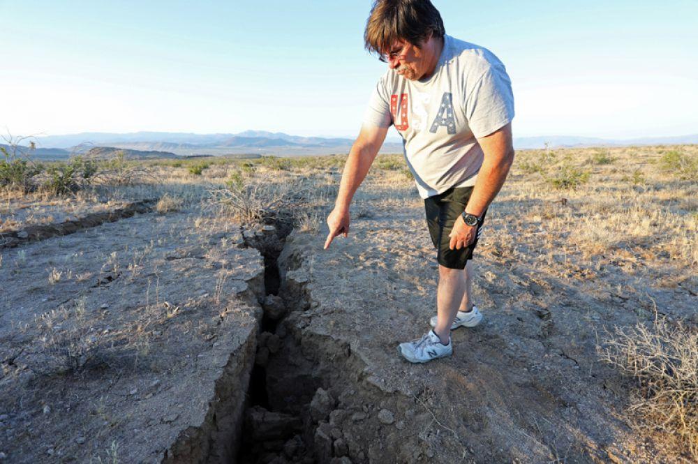 Мужчина показывает трещину, образовавшуюся в результате землетрясения.