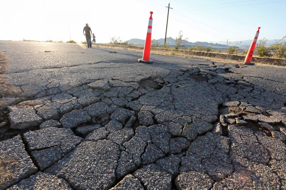 Трещины, образовавшиеся на шоссе во время мощного землетрясения в Южной Калифорнии неподалеку от города Риджкрест.