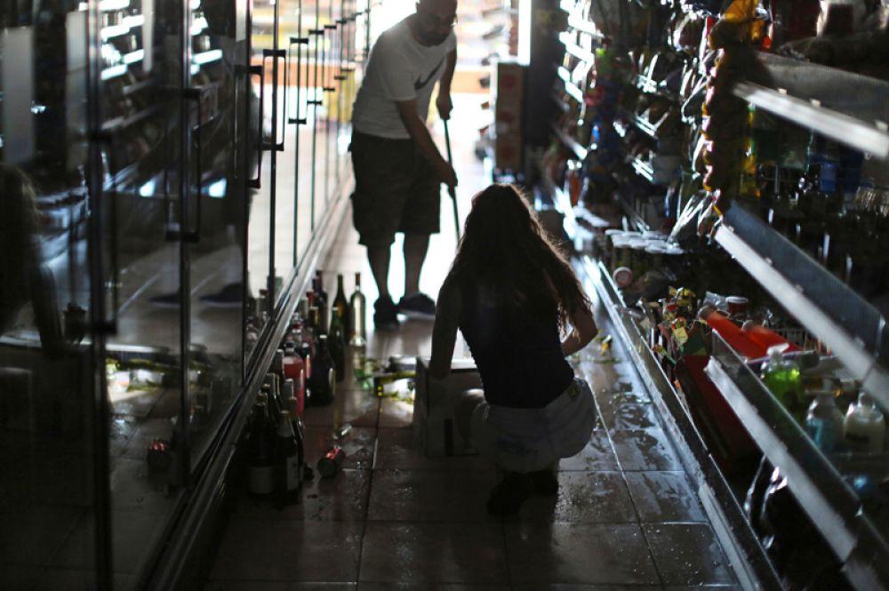 Люди убирают разбитые бутылки в винном магазине после мощного землетрясения в городе Риджкрест.