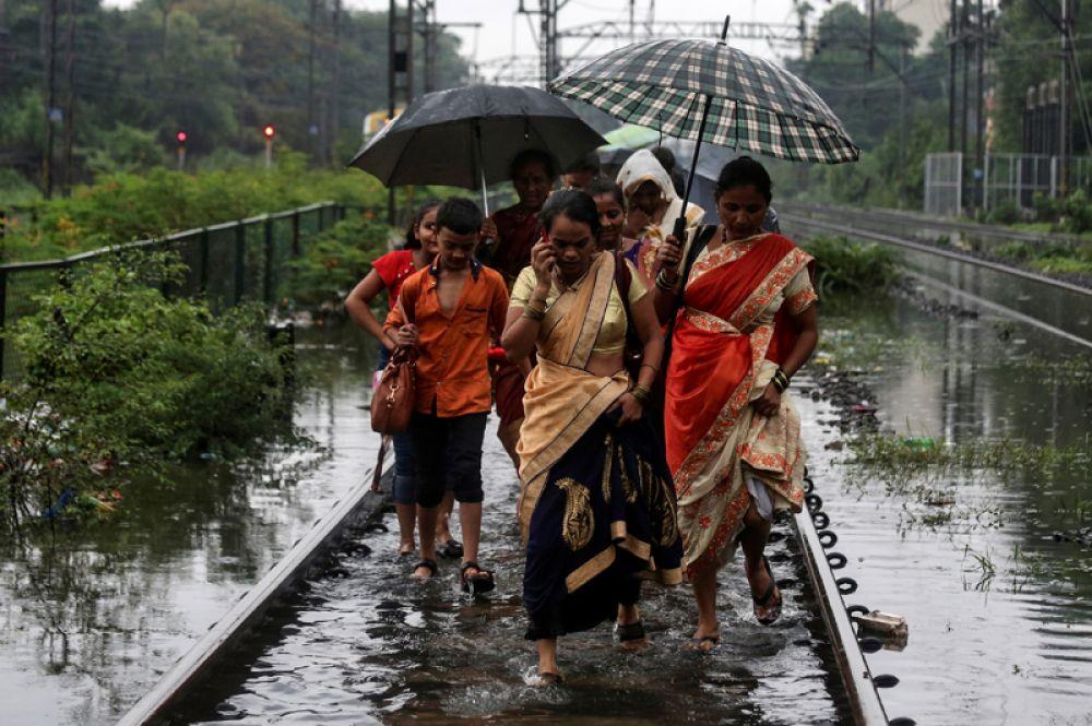Пассажиры идут по затопленным железнодорожным путям после остановки поезда во время сезона муссонных дождей в Мумбаи, Индия.