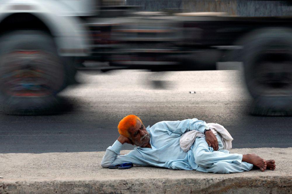 Мужчина отдыхает на дороге возле портовой зоны в Карачи, Пакистан.