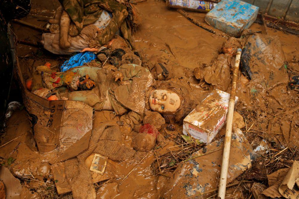 Личные вещи местных жителей лежат в грязи после сильного дождя в Тафалье.