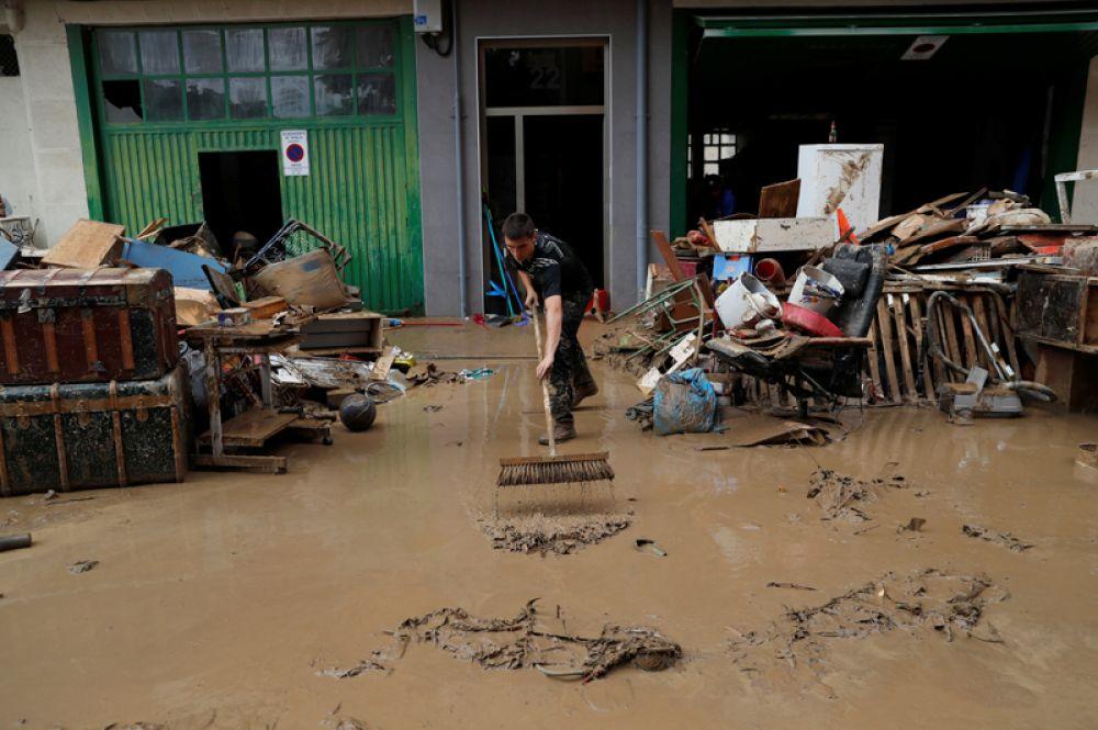 Мужчина убирает мусор после сильных дождей в Тафалье.
