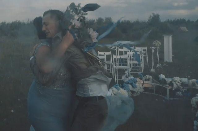 Свадебная церемония проходит в поле и начинается при плохой погоде. Далее ветер становится сильнее и начинается дождь, однако влюблённые продолжают идти к алтарю.