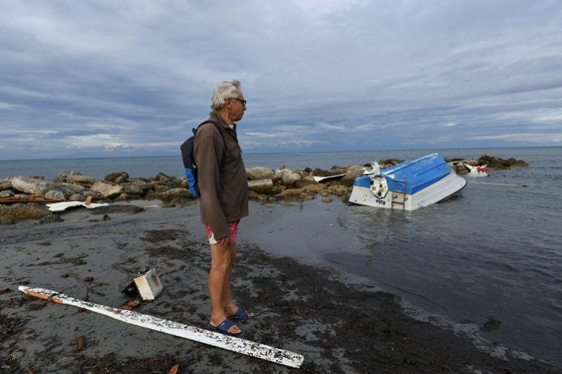 Рыбак смотрит на свою лодку, перевернувшуюся в результате шторма.