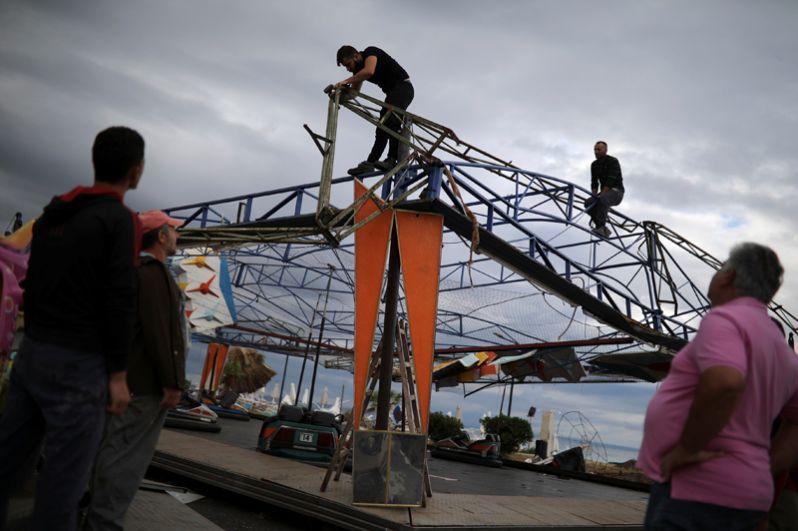 Мужчины делают ремонт в парке развлечений после шторма в деревне Неа Плагия.