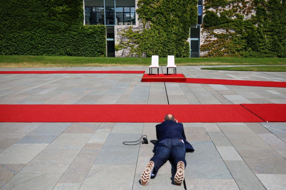 Мужчина фотографирует стулья, подготовленные для канцлера Германии Ангелы Меркель и премьер-министра Дании Метте Фредериксена перед их встречей в Берлине, Германия.