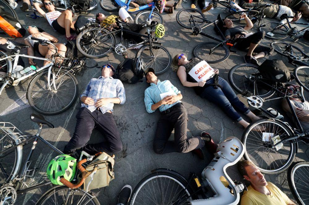 Люди принимают участие во флешмобе для привлечения внимания к травмам и смертельным случаям, случающихся с велосипедистами во время езды по дорогам Манхэттена в Нью-Йорке, США.