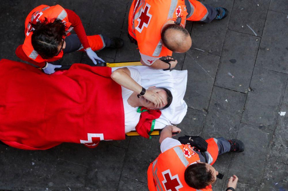 Медики уносят пострадавшего во время бега с быками на фестивале Сан-Фермин в Памплоне, Испания.
