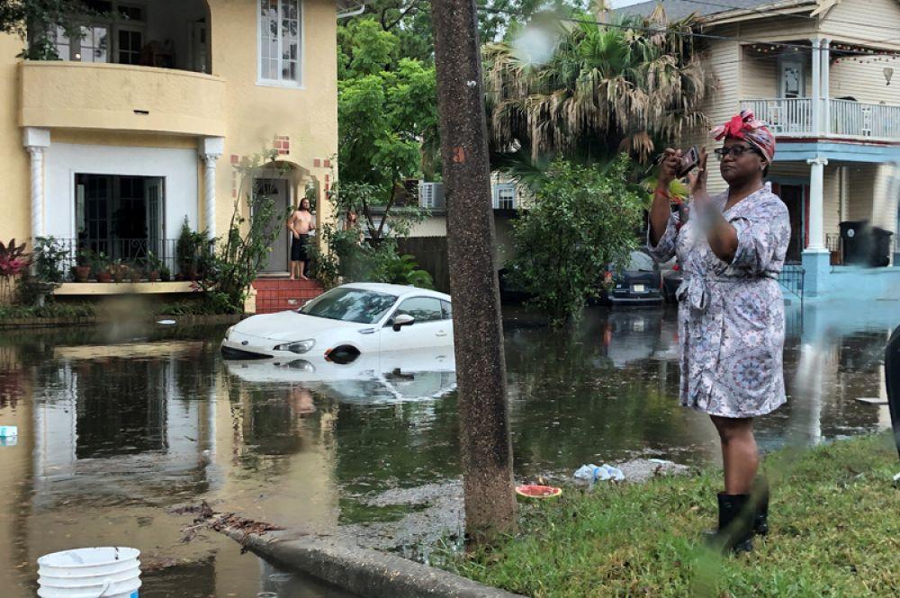 Женщина фотографирует затопленную улицу в Новом Орлеане, США.