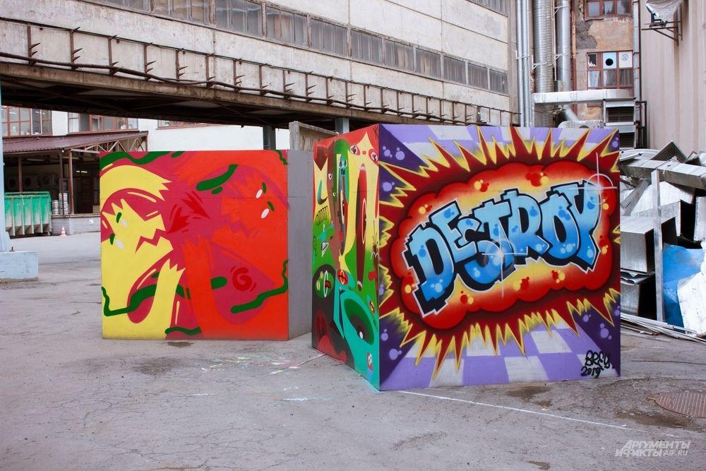 Работа команд RAYONS, главных популяризаторов граффити в городе по версии организаторов «Стенограффии», и DESTROYERS, представителей классического граффити. Рисунки сделаны на деревянных кубах и находятся на проспекте Ленина, 49, во дворе «Дома печати».