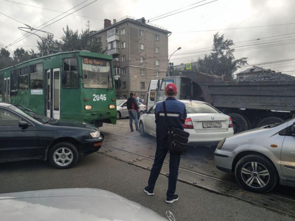 В центре перекрестка стояли трамвай, автомобиль скорой помощи, грузовики и легковушки