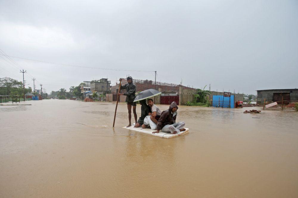 Местные жители используют самодельный плот, чтобы пересечь улицу в городе Агартала.