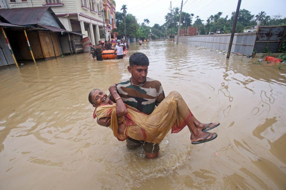 Мужчина несет пожилую женщину в безопасное место после проливных дождей в деревне Балдахал, на окраине города Агартала.
