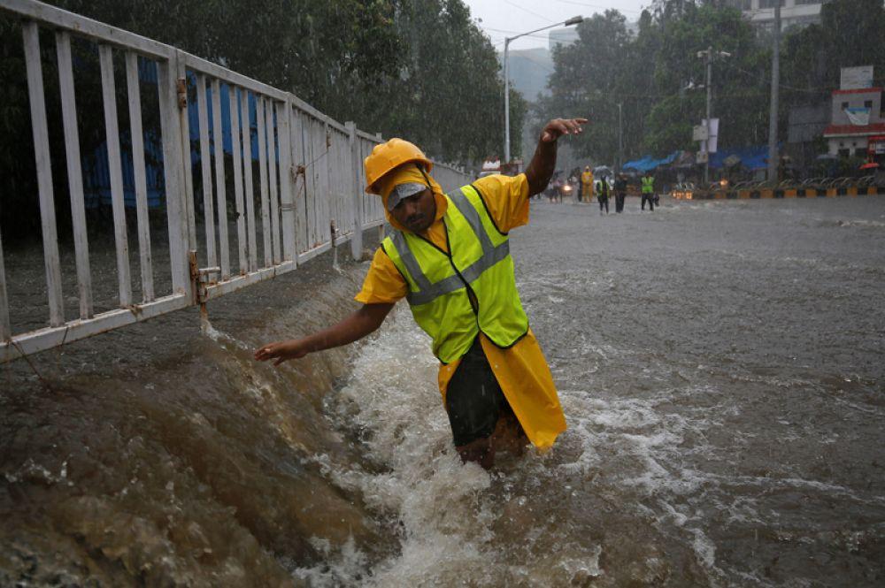 Волонтер на затопленной улице во время проливных дождей в Мумбаи.