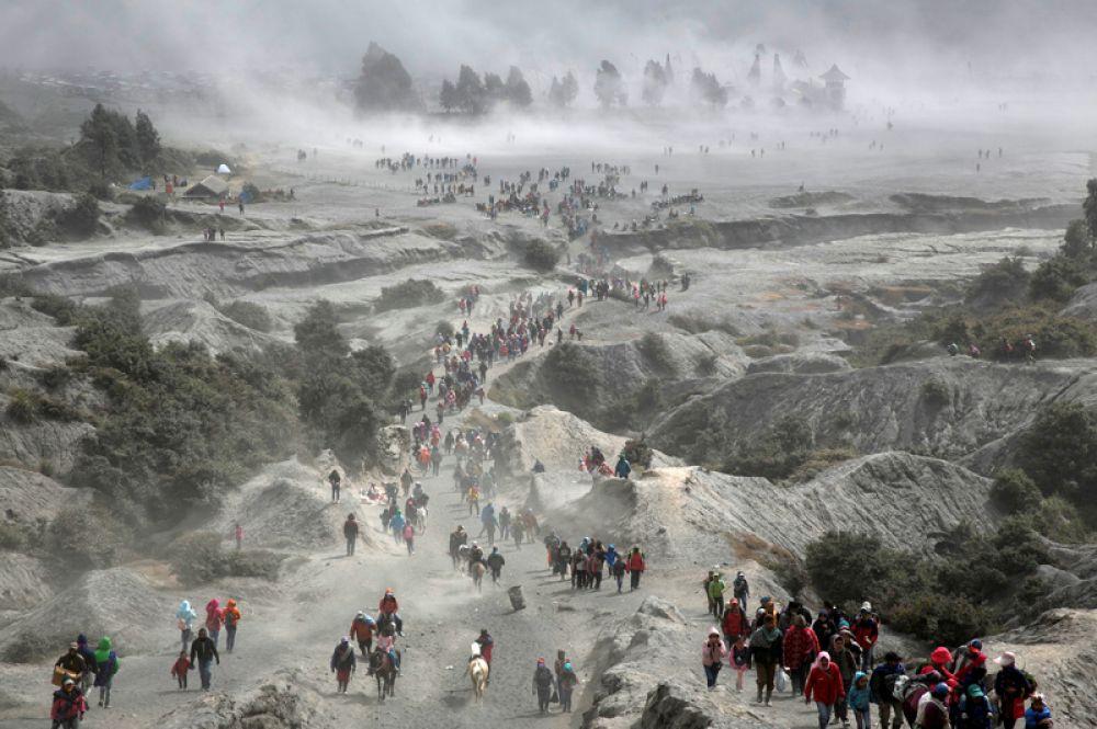 Люди поднимаются на вулкан Бромо на острове Ява в Индонезии для церемонии Касада, когда они совершают подношения богам.