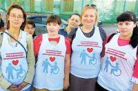 Женщина надели обычные белые майки с изображением взрослого, ребёнка в инвалидной коляске и алого сердца. Над картинкой – хэштеги.