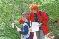 Жительница Ясенева Ольга Полянова помогает внуку найти описание пластиковой тарелки во время экологического квеста. Вприроде такой кусок пластика будет разлагаться от450 до1000 лет.
