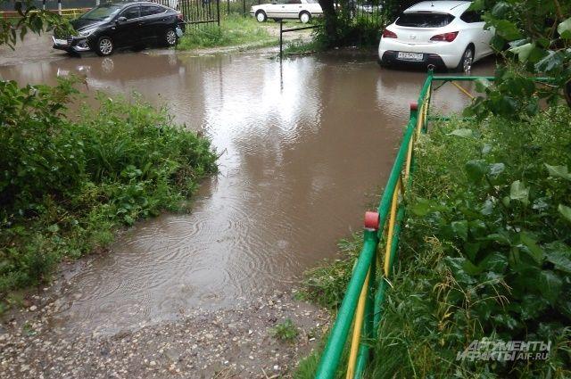 Из-за осадков вода в реке поднялась и вышла из берегов.