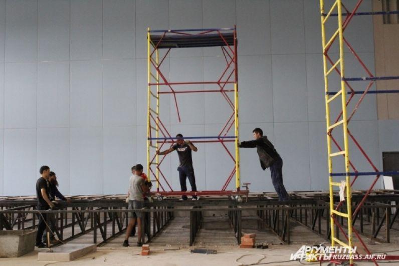Рабочие возводят сцену.