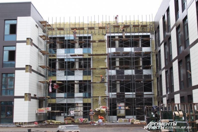 Рабочие заканчивают отделку фасадов зданий.