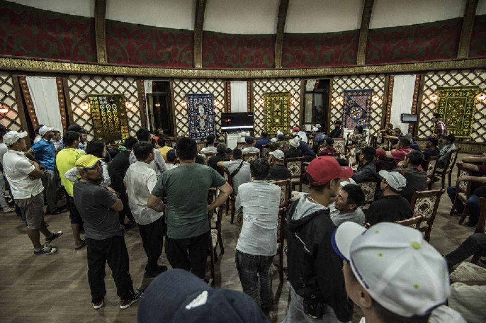 Люди смотрят новости на территории резиденции экс-президента Киргизии Алмазбека Атамбаева в селе Кой-Таш, где прошла спецоперация по его задержанию.