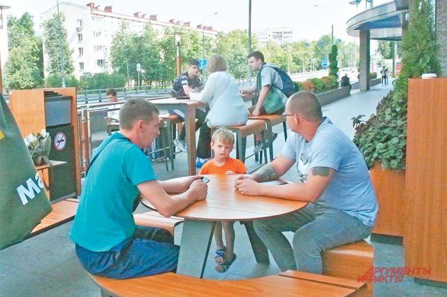 Летние кафе в районе посещают взрослые и дети.
