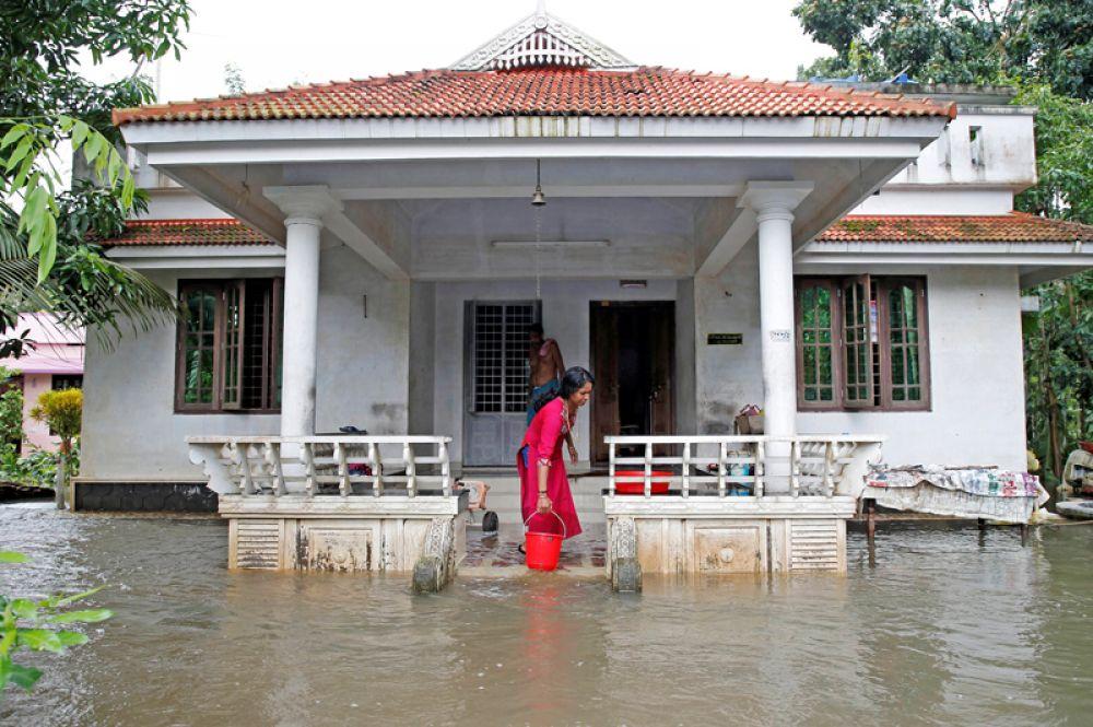 Женщина выгребает воду из затопленного дома на окраине Кочина в штате Керала.