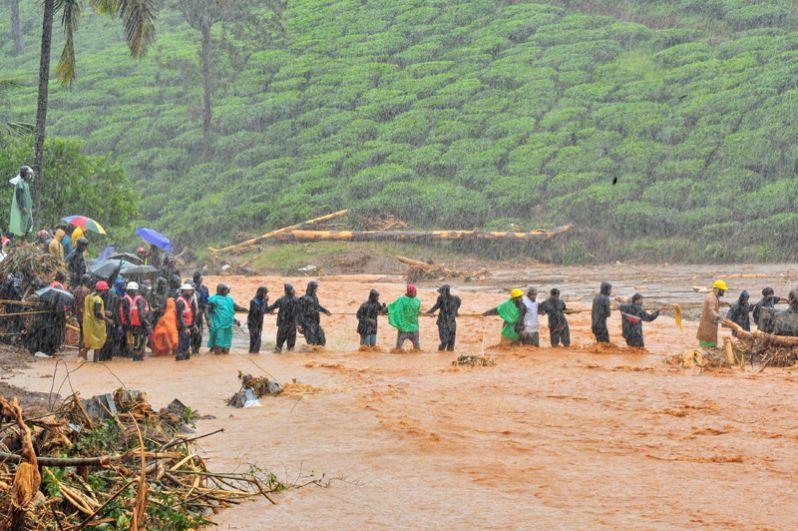 Спасатели помогают жителям пересечь затопленную территорию после оползня, вызванного проливными дождями в штате Керала.