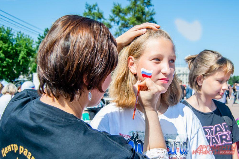 Желающим украсить себя российским флагом триколор с помощью грима рисовали на лице.