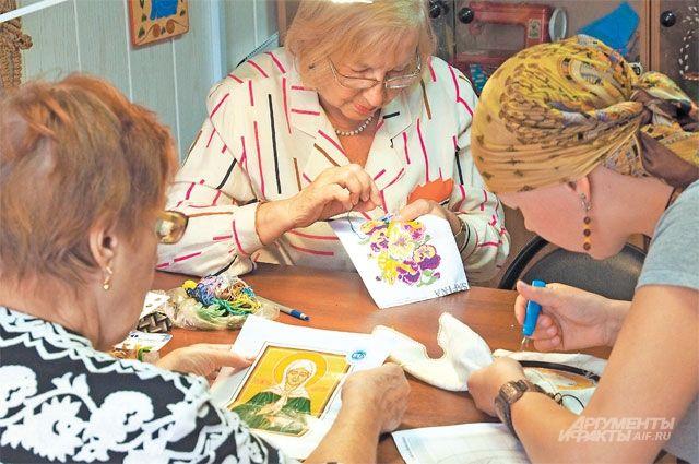Посетители студии вышивают кто натюрморты, кто иконы.