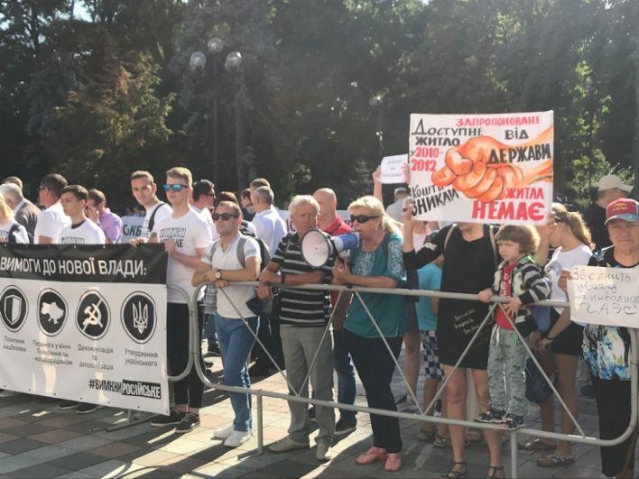 Около 09:00 утра, 29 августа, под зданием парламента, помимо журналистов, собрались митингующие, плакаты которых указывали на ошибки парламента с программой