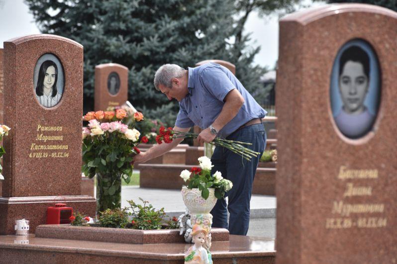 Мужчина принес цветы на могилу на мемориальном кладбище «Город ангелов» в Беслане, где похоронены погибшие во время теракта в 1-й Бесланской школе 1-3 сентября 2004 года.