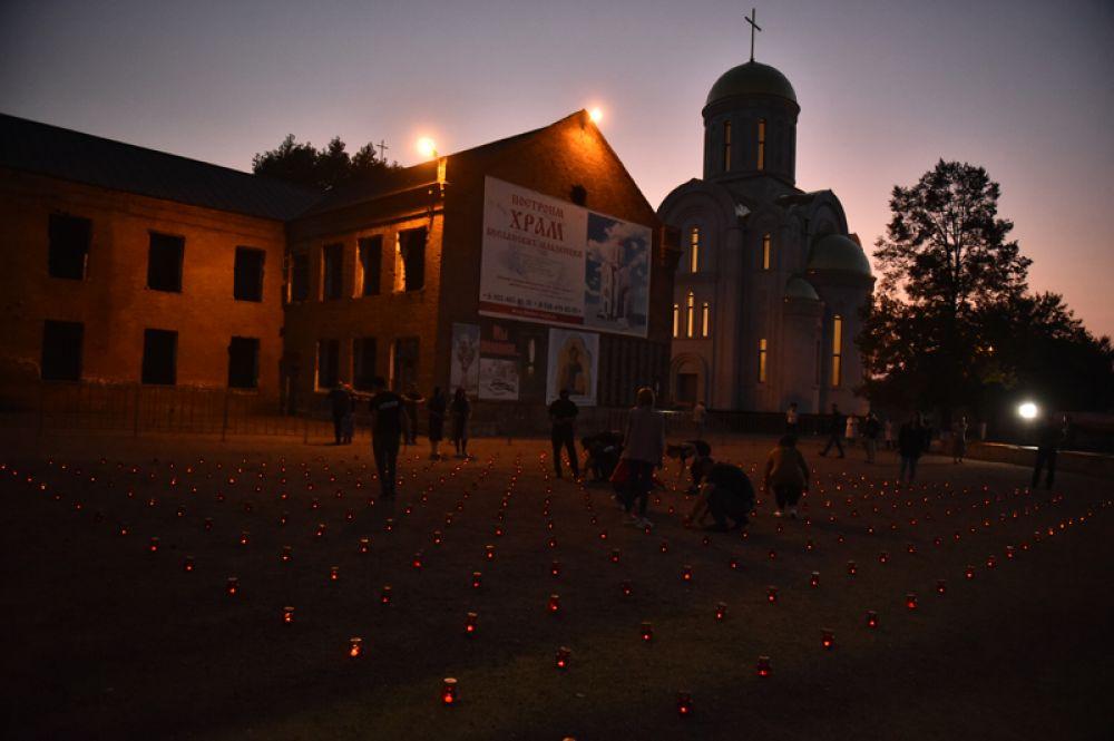 Жители зажигают свечи во дворе бывшей 1-й Бесланской школы в память погибших в теракте 1-3 сентября 2004 года.