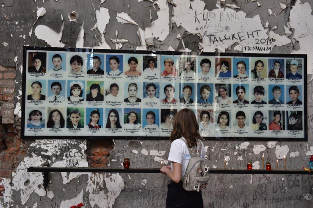 Школьница у стенда с портретами погибших в бывшей 1-й Бесланской школе, где проходят траурные мероприятия, посвященные 15-й годовщине теракта 1-3 сентября 2004 года.