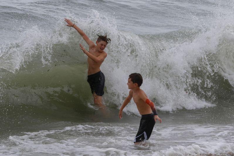 Мальчики купаются в высоких волнах в городе Бока-Ратон во Флориде.