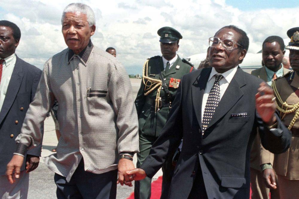 Президент Зимбабве Роберт Мугабе с южноафриканским коллегой Нельсоном Манделой во время визита последнего в Зимбабве, 1998 год.
