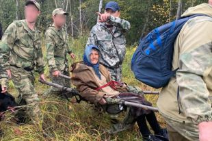 На самодельных носилках женщину вынесли из леса.