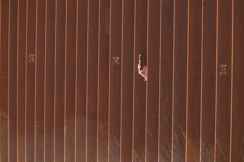 Человек фотографирует Трампа во время его визита к стене на границе США и Мексики.