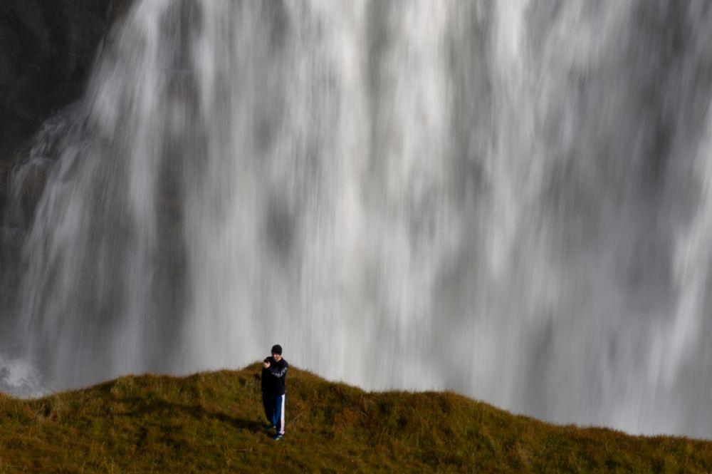 Турист делает селфи в зоне, где запрещено ходить, на фоне водопада Гульфосс в Исландии.